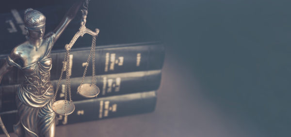Lady justice holding scales in front of legal books