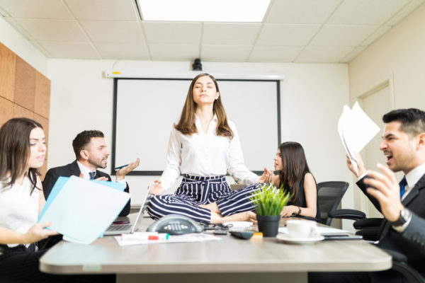 Woman sitting on a conference table meditating while others compete for her attention.