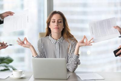 Calm female manager meditating taking break avoiding stressful job